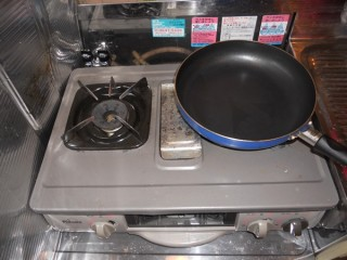 A Japanese gas stove with fry pan on top