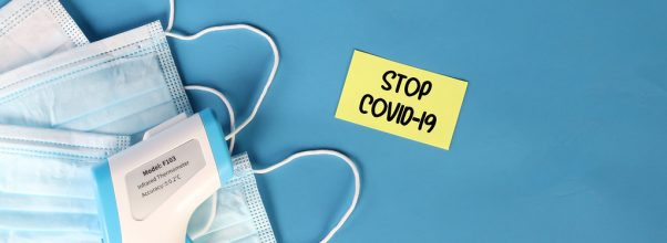 "Surgical masks, thermometer, and note that says ""Stop COVID-19"""